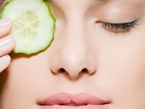 Woman using cucumber on eyes