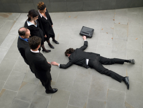 man lying on floor while others watch