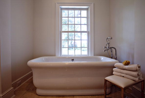 "A bathtub sits in the ""hers"" bathroom in the master suite of"