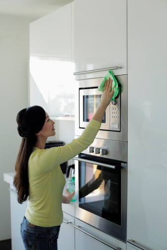 Girl cleaning Microwave