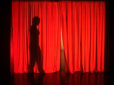 Female silhouette behind theatrical red curtains