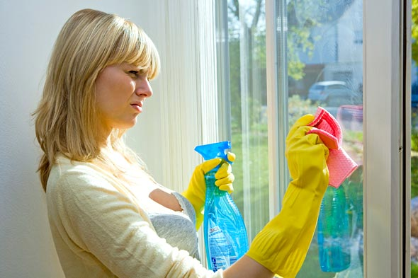 Cleaning windows with glass cleaner