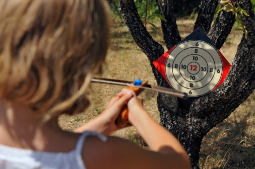 Girl aiming a target with crossbow, in garden