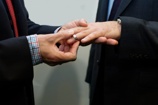Man putting wedding ring on another man's finger