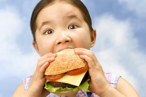 Little girl munching on a large burger