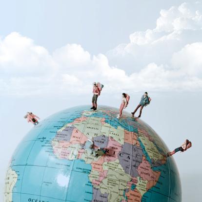 Miniature figures of people on globe