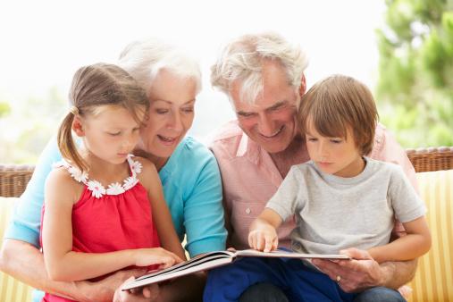 Grandparents And Grandchildren Reading Book On Garden Seat