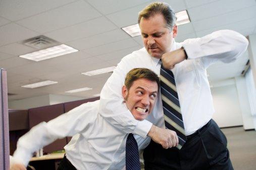 Two businessmen fighting in office, one in headlock