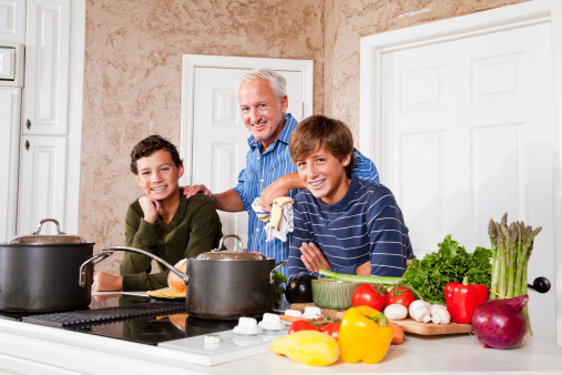 Father and teenage sons in kitchen by stove