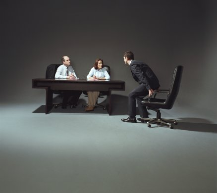 Young businessman being interviewed by two people