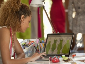 Mixed race clothing designer using laptop in workshop