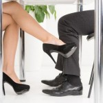 womans-foot-looking-mans-foot-under-business-table